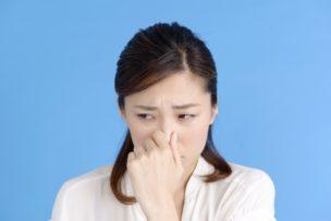 女性が臭いに鼻をつまんでいる